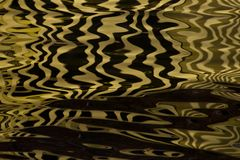 Waves on the water forming stripes similar to the texture of velvet, the alternation of gold and black stripes and waves. Golden water Waves on the water forming royalty free stock photo