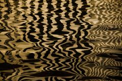 Waves on the water forming stripes similar to the texture of velvet, the alternation of gold and black stripes and waves. Golden water Waves on the water forming stock photos