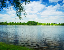 Waves on water of lake and green trees Royalty Free Stock Photos