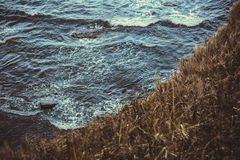 Waves. Water sea ocean wave nature grass yellow darkly hight mountains Stock Images