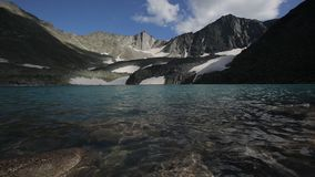 Waves splashing against the stones. Turquoise water of Upper Akchan lake. Mountain Altai landscape