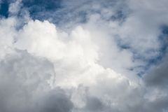 Waves of white fluffy clouds against the blue sky stock images