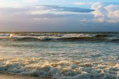 Waves and wind at sunset, stormy sea at sunset royalty free stock photo