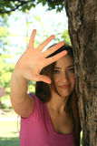 Waving. A young woman stands next to a tree, raising her palm in front of her in a wave Stock Image
