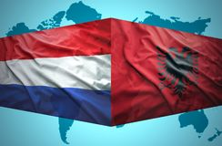 Waving Albanian and Dutch flags. Of the political map of the world Stock Images