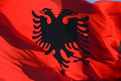 Waving Albanian red silk flag with printed black eagles in the center. Against the sky stock image