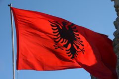 Waving Albanian red silk flag with printed black eagles in the center. Against the sky royalty free stock photos