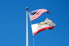 Waving American and California state flag in the breeze under a bright blue sky. The waving flags of America and California in front of a strong blue sky in San royalty free stock photo