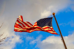 Waving American flag against a blue sky background. US flag sky Royalty Free Stock Image