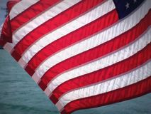 Waving American flag. American flag waving in front of water on sunny day Royalty Free Stock Image