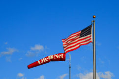 Waving American flag with LifeNet wind sock Royalty Free Stock Photos