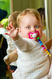 Waving baby with soother Royalty Free Stock Image