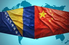 Waving Bosnian and Chinese flags. Of the political map of the world Royalty Free Stock Photo