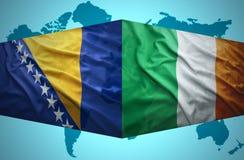 Waving Bosnian and Irish flags Stock Photos