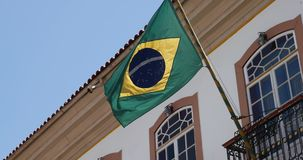 Waving Brazilian flag from a Colonial house in Ouro Preto, Brazil stock video