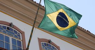 Waving Brazilian flag from a Colonial house in Ouro Preto, Brazil stock footage