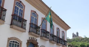 Waving Brazilian flag from a Colonial house in Ouro Preto, Brazil stock video footage