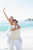 Waving bride getting a piggy back from husband smiling at camera Stock Photos