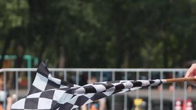 Waving checkered race flag close up. Flag which announces the final lap of the race on a finish line