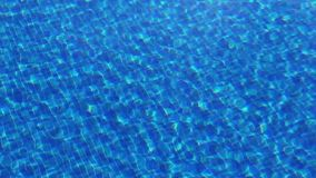 Waving clear water in swimming pool with blue bottom, top view stock video