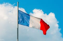 Waving colorful France flag on blue sky. Stock Photos