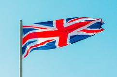 Waving colorful Great Britain flag on blue sky. Stock Photography