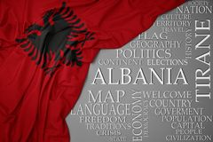 Waving colorful national flag of albania on a gray background with important words about country. Concept royalty free stock photos