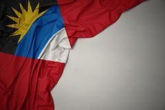 Waving national flag of antigua and barbuda on a gray background. Waving colorful national flag of antigua and barbuda on a gray background royalty free stock images