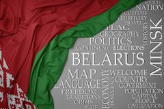 Waving colorful national flag of belarus on a gray background with important words about country. Concept stock photography