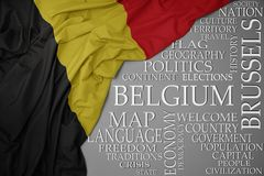 Waving colorful national flag of belgium on a gray background with important words about country. Concept stock images