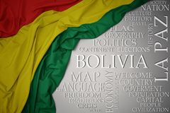 Waving colorful national flag of bolivia on a gray background with important words about country. Concept royalty free stock image
