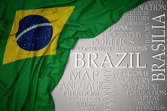Waving colorful national flag of brazil on a gray background with important words about country. Concept stock photo