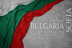 Waving colorful national flag of bulgaria on a gray background with important words about country. Concept royalty free stock image