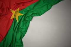 Waving national flag of burkina faso on a gray background. Waving colorful national flag of burkina faso on a gray background royalty free stock image