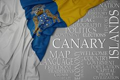 Waving colorful national flag of canary islands on a gray background with important words about country. Concept royalty free stock photo