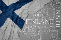 Waving colorful national flag of finland on a gray background with important words about country. Concept stock image