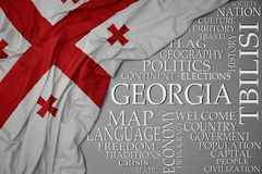 Waving colorful national flag of georgia on a gray background with important words about country. Concept royalty free stock photography