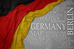 Waving colorful national flag of germany on a gray background with important words about country. Concept stock images