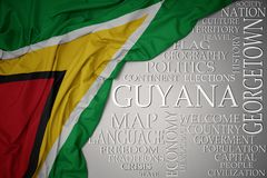 Waving colorful national flag of guyana on a gray background with important words about country. Concept royalty free stock photo