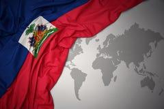 Waving colorful national flag of haiti. Waving colorful national flag of haiti on a gray world map background stock image