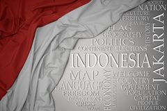 Waving colorful national flag of indonesia on a gray background with important words about country. Concept royalty free stock photos