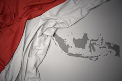Waving colorful national flag and map of indonesia. Waving colorful national flag of indonesia on a gray map background stock image