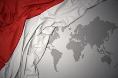 Waving colorful national flag of indonesia. Waving colorful national flag of indonesia on a gray world map background stock photos