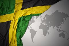 Waving colorful national flag of jamaica. Waving colorful national flag of jamaica on a gray world map background royalty free stock photography