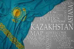Waving colorful national flag of kazakhstan on a gray background with important words about country. Concept royalty free stock images
