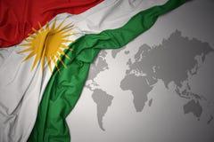 Waving colorful national flag of kurdistan. Waving colorful national flag of kurdistan on a gray world map background Stock Photo
