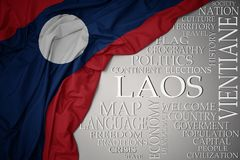 Waving colorful national flag of laos on a gray background with important words about country. Concept royalty free stock photography