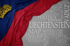 Waving colorful national flag of liechtenstein on a gray background with important words about country. Concept royalty free stock image