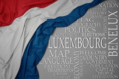 Waving colorful national flag of luxembourg on a gray background with important words about country. Concept royalty free stock images