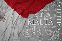 Waving colorful national flag of malta on a gray background with important words about country. Concept royalty free stock photos